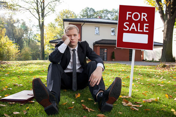 Dejected real estate agent sitting in front of house next to for sale sign