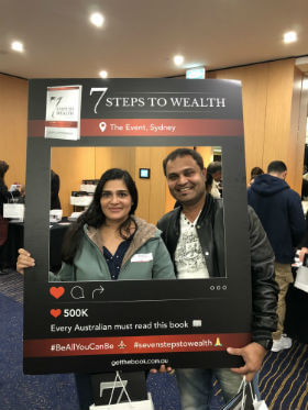 a couple is carrying their gift from 7 steps to wealth event in Sydney