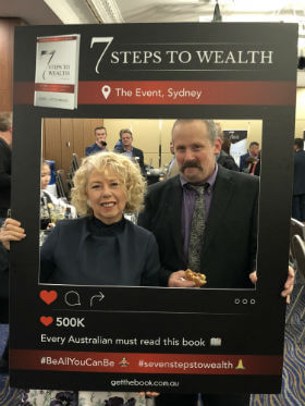 a happy couple is taking their photo when they attend 7 Steps to wealth event