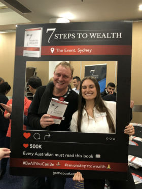 a man is smiling with a 7 steps to wealth book on his hand in property investment seminar
