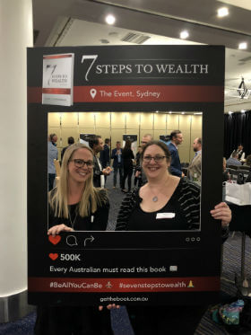2 women is taking great photo with 7 Steps to wealth frame in Sydney property investment seminar