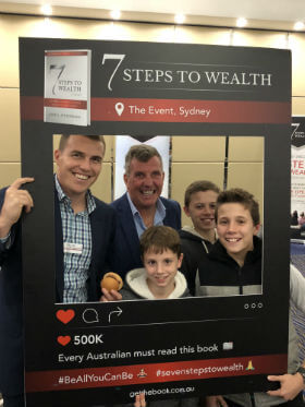 a man taking photo with his 3 children is happy at 7 steps towealth property investment seminar