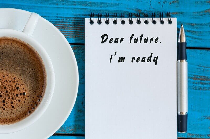 a notebook written of readiness for future and a cup of coffee