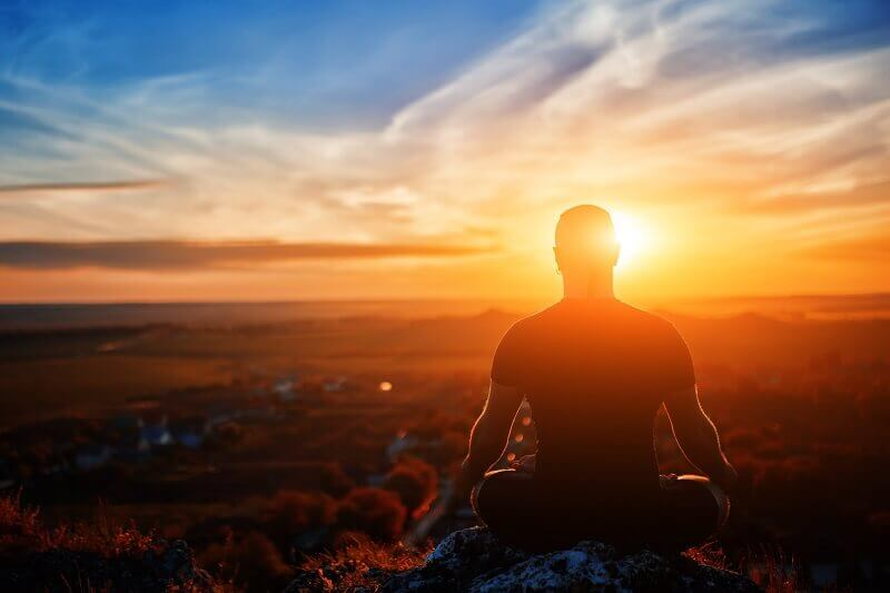 a man is sitting at sunrise and thinking of his reason to set goals for his life