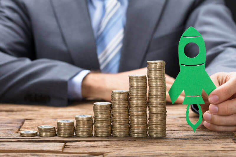 businessman holding green paper rocket on stacked coins arranged in increasing order