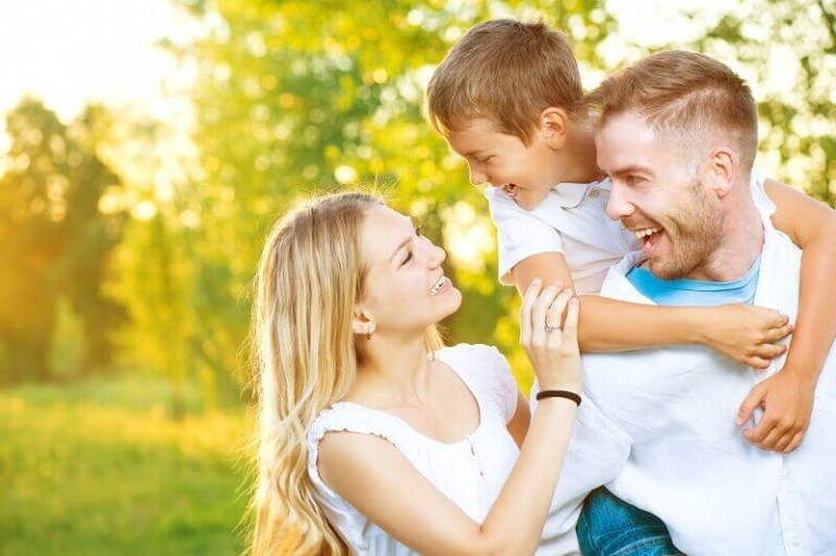 Happy joyful young family father, mother and little son having fun outdoors, playing together in summer park, countryside